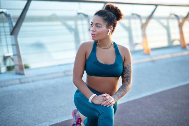 schöne frau mit tattoo auf arm dehnung nach dem training - damen leggings übergrößen stock-fotos und bilder