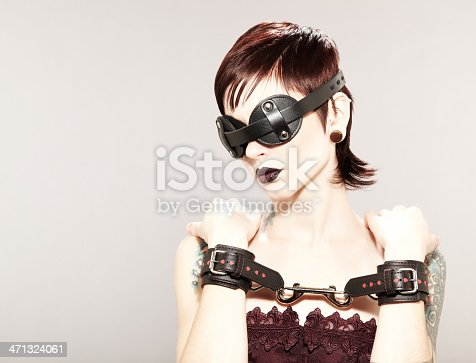 Sexy young female model with a tattoo on her neck wearing dark makeup and a leather blindfold and handcuffs.  Horizontal shot.
