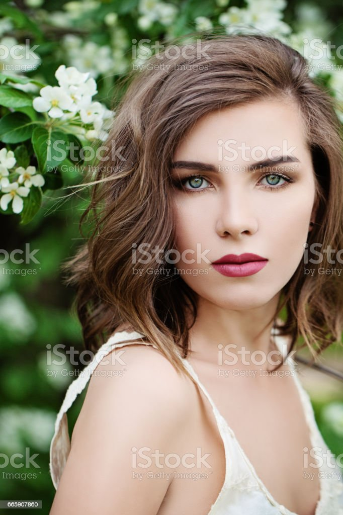 Beautiful Woman with Wavy Hair on Spring Blossom Background foto stock royalty-free