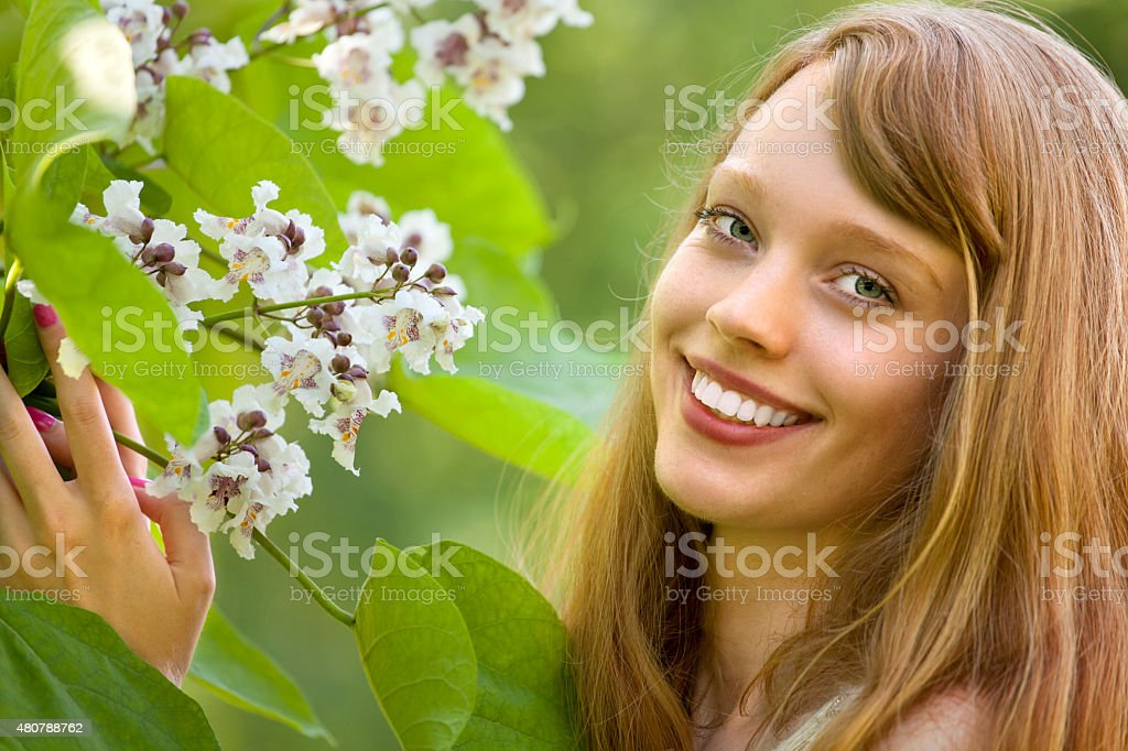 Beautiful woman with white flower of Catalpa Tree stock photo