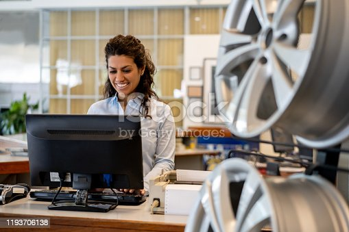 Beautiful woman working at the reception of an auto repair shop looking at computer screen very cheerfully  and smiling