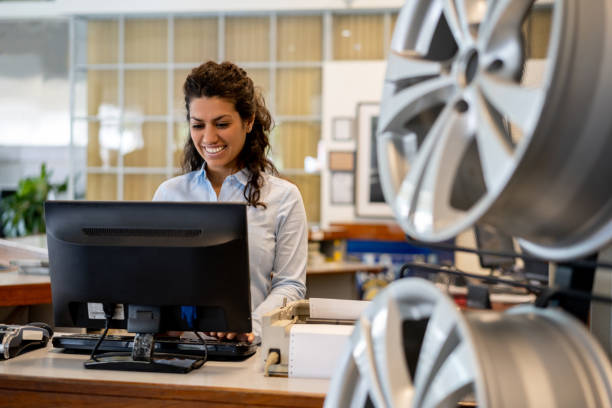 Beautiful woman working at the reception of an auto repair shop looking at computer screen very cheerfully Beautiful woman working at the reception of an auto repair shop looking at computer screen very cheerfully  and smiling cheap stock pictures, royalty-free photos & images