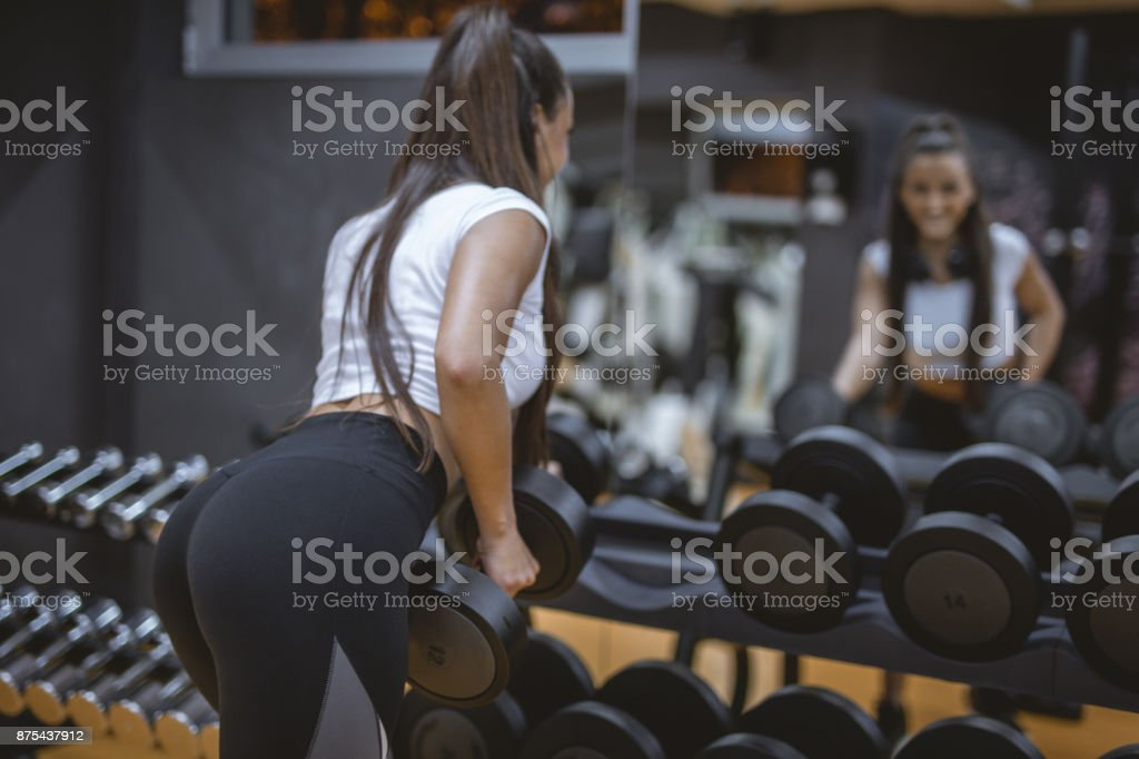Beautiful woman working out with weights in a gym stock photo