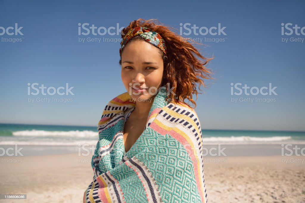 Portrait of beautiful mixed race woman wrapped in blanket standing on...