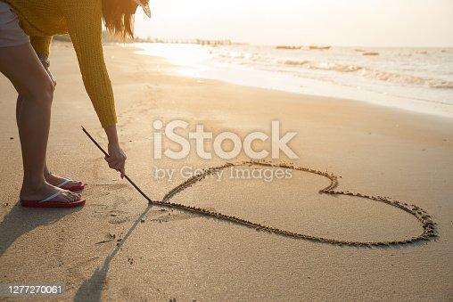 Beautiful woman writing message (heart symbol) on sand beach to her friend or boyfriend.