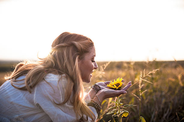 Beautiful womanl with sunflower outdoors stock photo