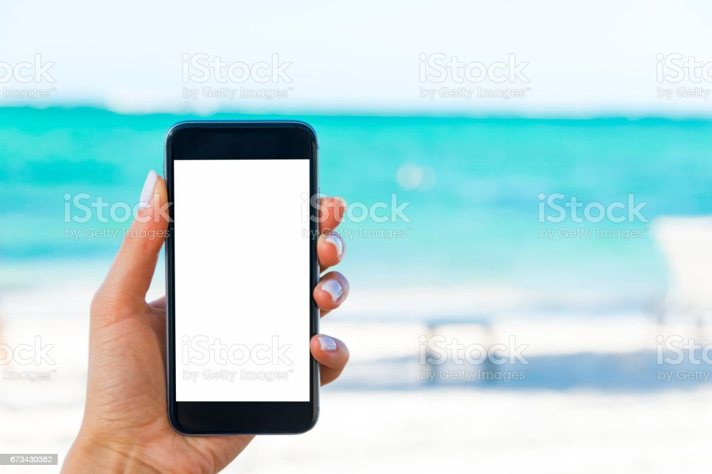 Beautiful woman's hand using smart phone at beach. Smartphone white screen.Blank empty screen stock photo