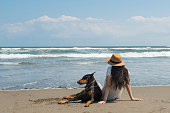 美しい女性とドーベルマンはビーチでリラックスします。