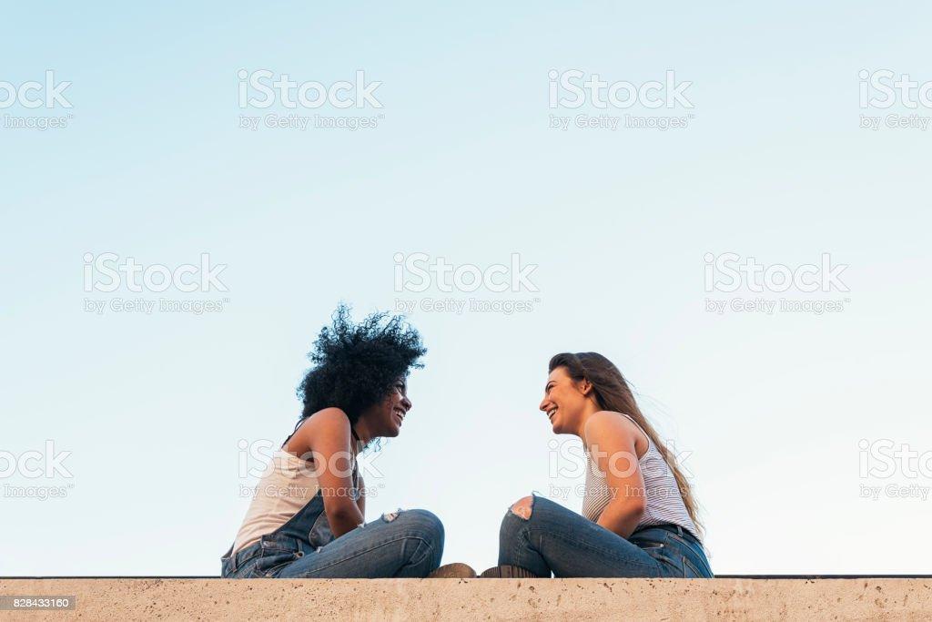 Beautiful women chatting in the street. stock photo