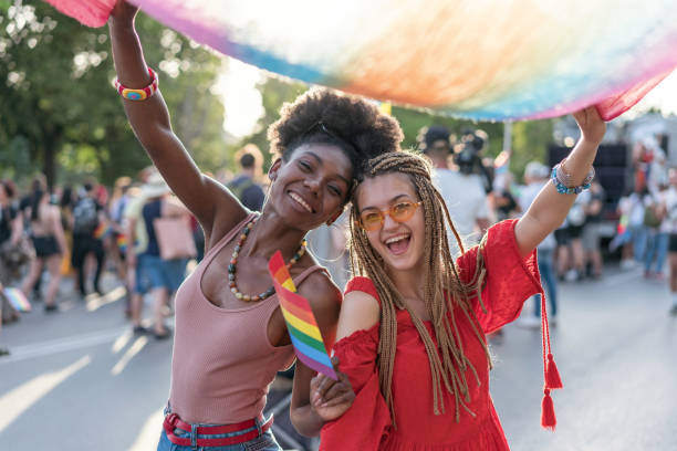 Beautiful women dancing and waving rainbow scarf at the pride parade stock photo