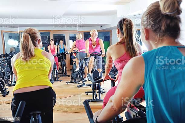 Hermosa Mujer Haciendo Ejercicio En Una Clase De Spinning En El Gimnasio Foto de stock y más banco de imágenes de Clase de bicicleta estática