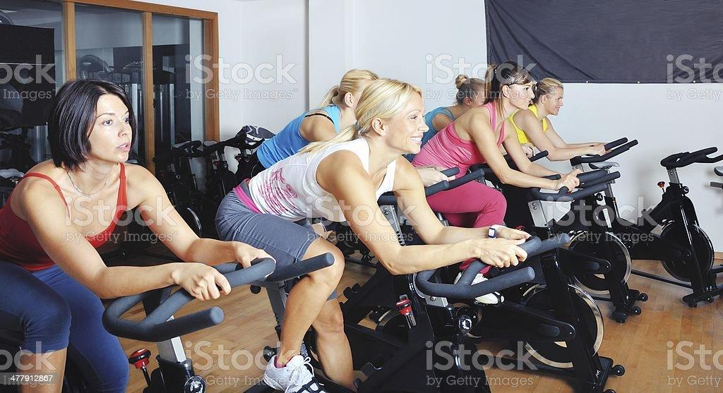 Hermosa mujer haciendo ejercicio en una clase de spinning en el gimnasio - Foto de stock de Clase de bicicleta estática libre de derechos