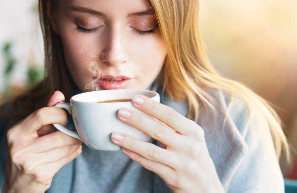 Beautiful women drink hot coffe Cafe, Winter, Women, Coffee - Drink, Sunset caffeine stock pictures, royalty-free photos & images