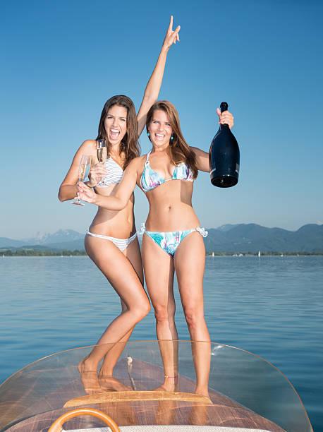 schöne frau trinkt champagner auf einem boot deck - bayerische brotzeit stock-fotos und bilder