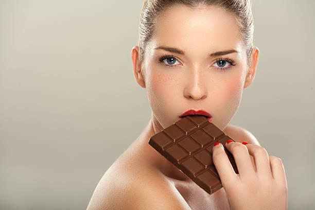 schöne frauen essen schokoladen-bar - marko skrbic stock-fotos und bilder