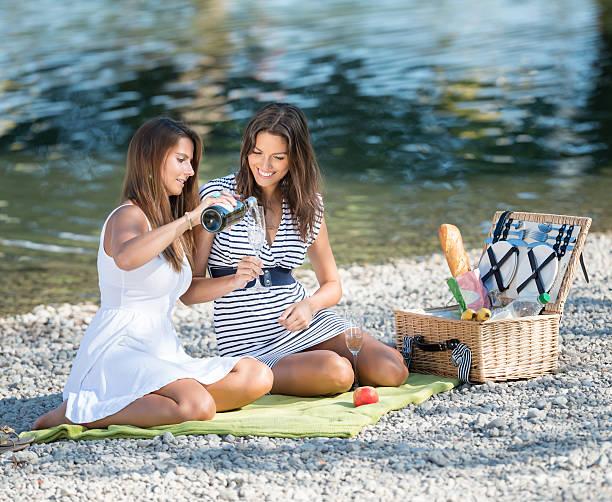 schöne frauen mit einem picknick am see - bayerische brotzeit stock-fotos und bilder
