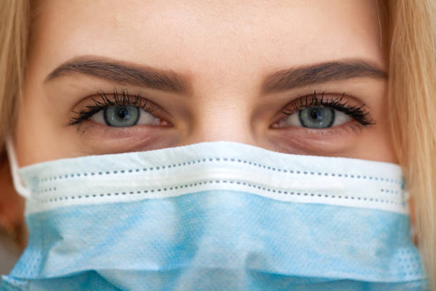 Beautiful Women In A Medical Mask. Blond young woman wearing medical mask adjusting it with her hands close up Beautiful Women In A Medical Mask. Close-up of a young woman with a surgical mask on her face against SARS-cov-2. pollution mask stock pictures, royalty-free photos & images