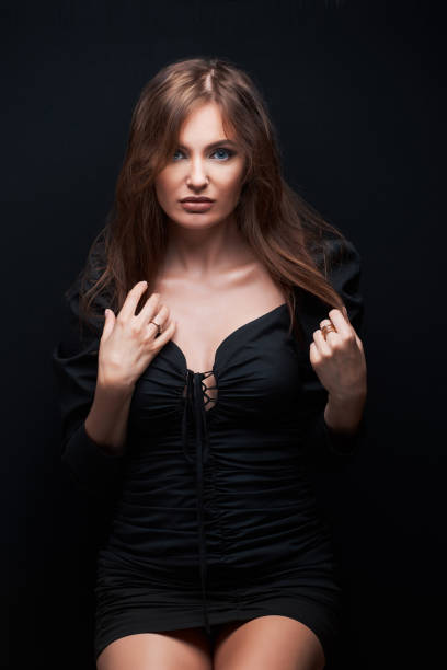 beautiful women in dark dress posing over dark backgroun, beautiful brown hair stock photo