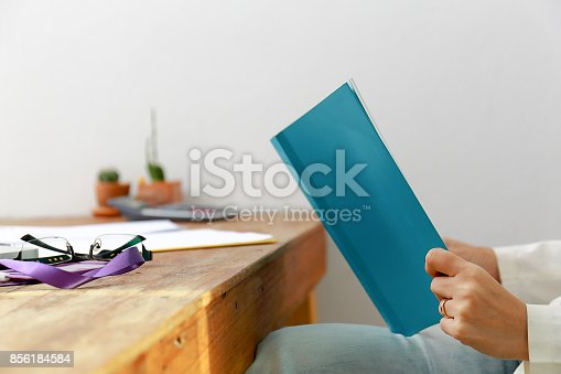 839809942istockphoto Beautiful women reading magazines in a quiet white office. 856184584