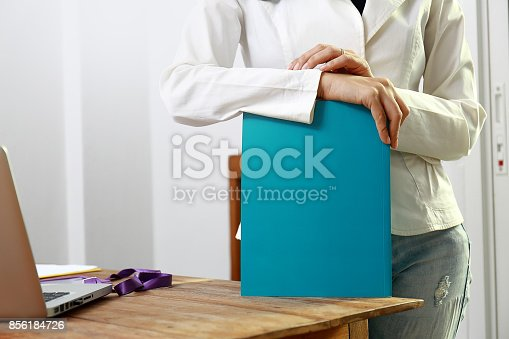 839809942istockphoto Beautiful women reading magazines in a quiet white office. 856184726