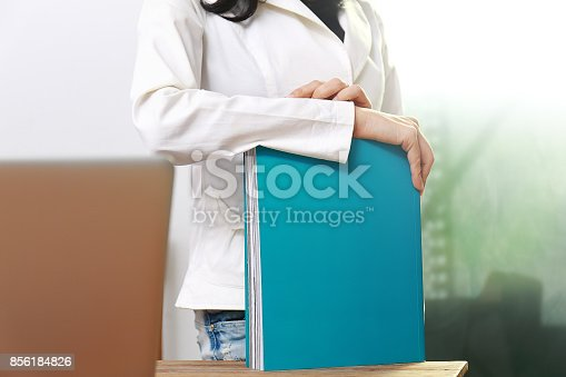 839809942istockphoto Beautiful women reading magazines in a quiet white office. 856184826