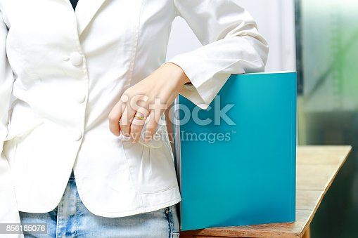 839809942istockphoto Beautiful women reading magazines in a quiet white office. 856185076