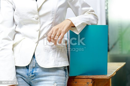 839809942istockphoto Beautiful women reading magazines in a quiet white office. 856185132