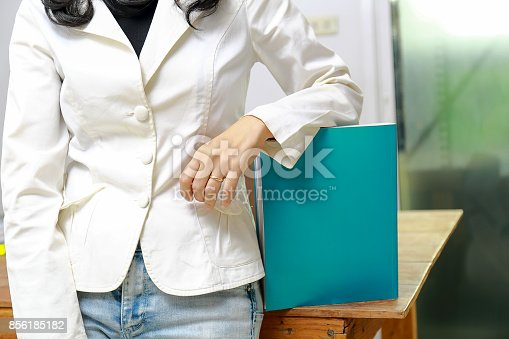 839809942istockphoto Beautiful women reading magazines in a quiet white office. 856185182