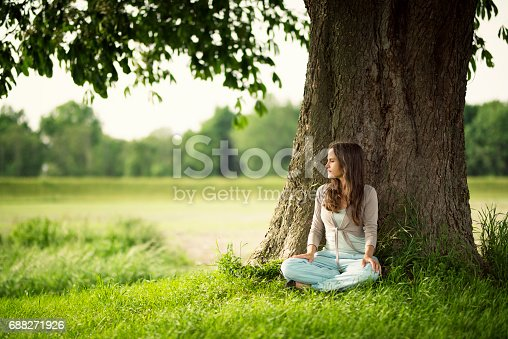 Beautiful caucasian women with long brown hair sit and relax under a chestnut-tree. Vibrant colors - evening sun.