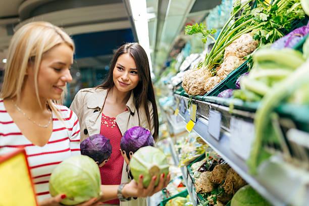 schöne frauen einkaufen gemüse und obst - bio lebensmittel stock-fotos und bilder
