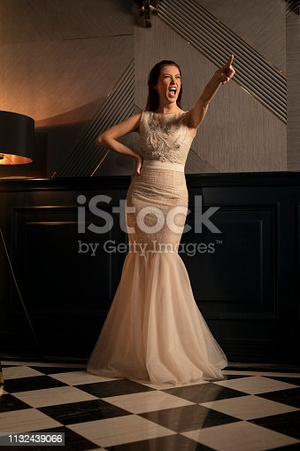 Beautiful women singer, singing, hand up, celebrations.  Fashion portrait, young women dressed elegantly lifestyles. in a luxury interior.