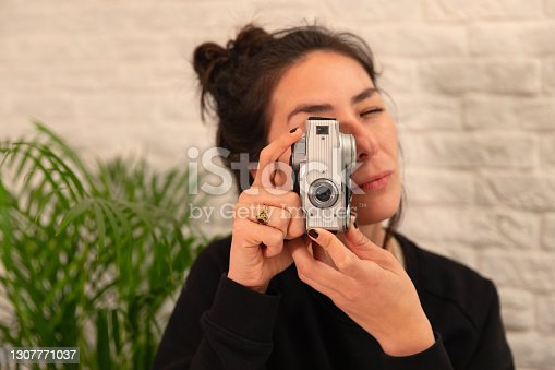 Beautiful women takes picture with analog camera