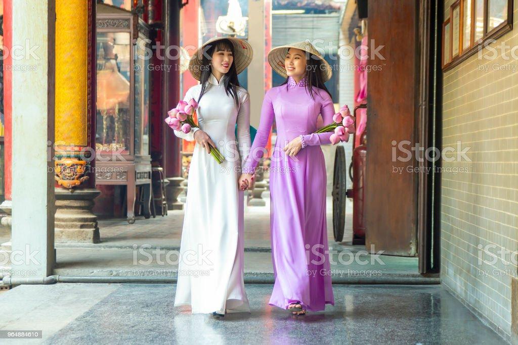 美麗的婦女與越南文化傳統禮服, Ao 傣族是著名的傳統服裝, 胡志明越南。 - 免版稅一起圖庫照片