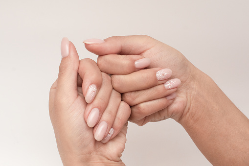 Beautiful women's hands with delicate pink beautiful manicure with patterns. Concept of well-groomed hands in a beauty salon from nail master.