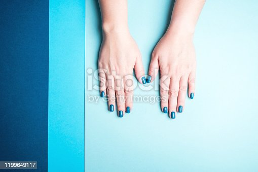 1128559926 istock photo Beautiful women's hands with stylish blue manicure 1199649117