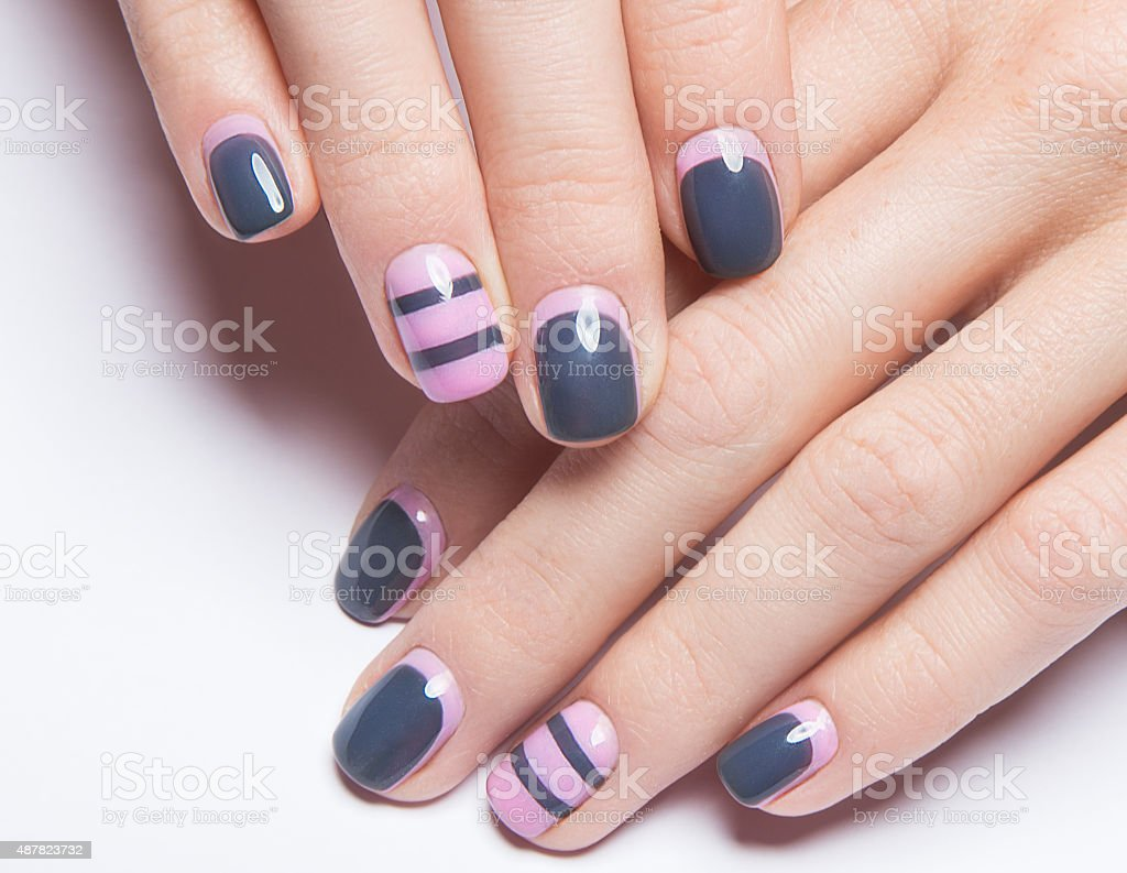 Beautiful women's manicure with gray and pink polish on stock photo
