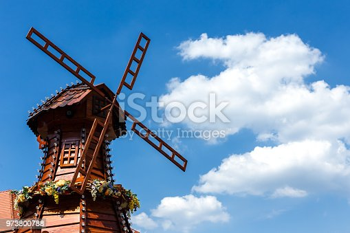 Beautiful wooden mill decorated with flowers and light bulbs is spinning on a blue cloudy sky background.