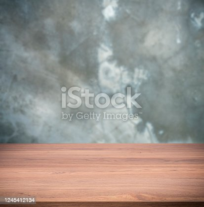 Beautiful wooden table over blur concrete wall background