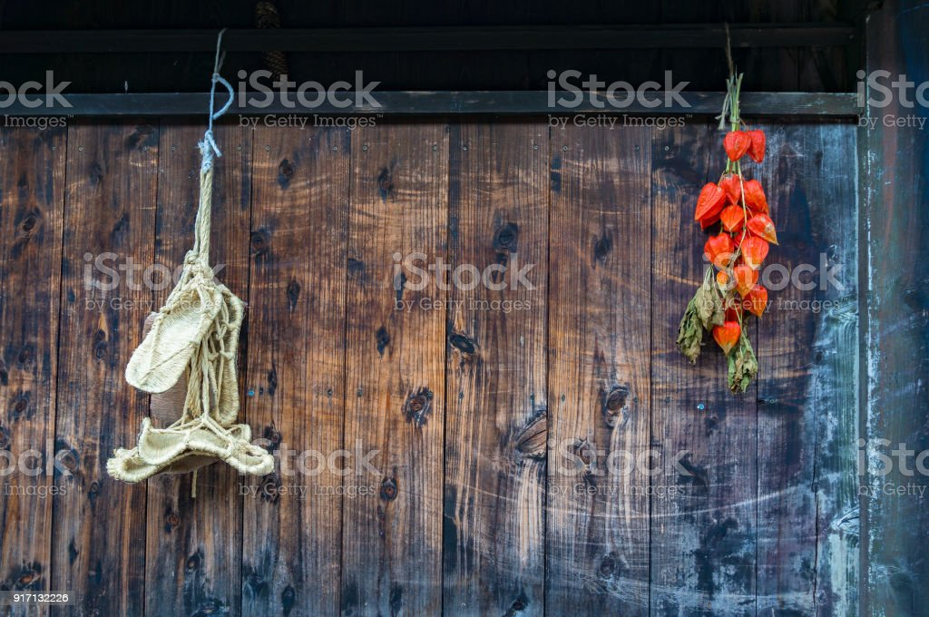 Beautiful wooden wall with bright physalis pods and traditional Japanese straw sandals stock photo