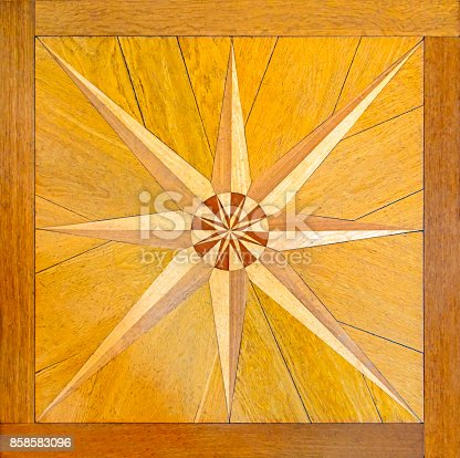 Marquetry or intarsia on parquet flooring. Crafted wind rose on beautiful woodworks. Star shape symbol within a wooden frame.