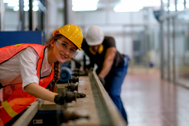 Beautiful worker or technician or engineer woman smile and look forward in front of rail of the machine with her co-worker as background in factory Beautiful worker or technician or engineer woman smile and look forward in front of rail of the machine with her co-worker as background in factory. apprentice stock pictures, royalty-free photos & images