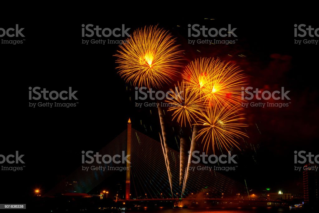 Beautiful yellow and red color firework display for celebration happy new year and merry christmas in the night sky, bangkok city, thailand stock photo