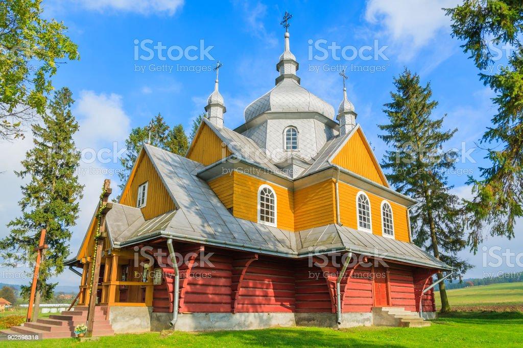Beautiful yellow old wooden orthodox catholic church in Gladyszow village, Beskid Niski Mountains, Poland stock photo