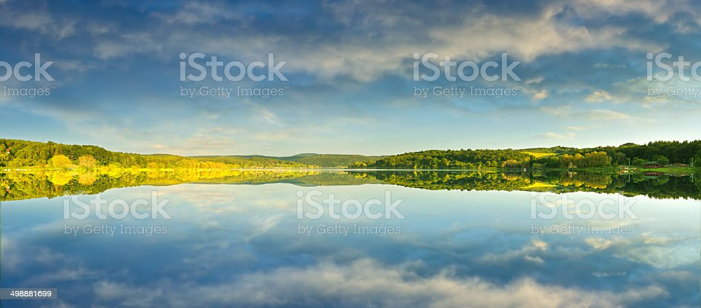 Beautiful yellow rape field, reflected in the lake, stock photo