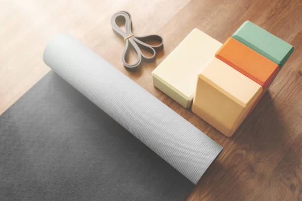 Beautiful yoga equipment composition of mat, bricks and rubber band. Morning mood, sunlight stock photo