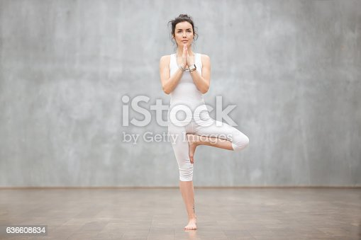 Portrait of beautiful young woman wearing white sportswear working out against grey wall, doing yoga or pilates exercise. Standing in Vrksasana, Tree pose. Full length