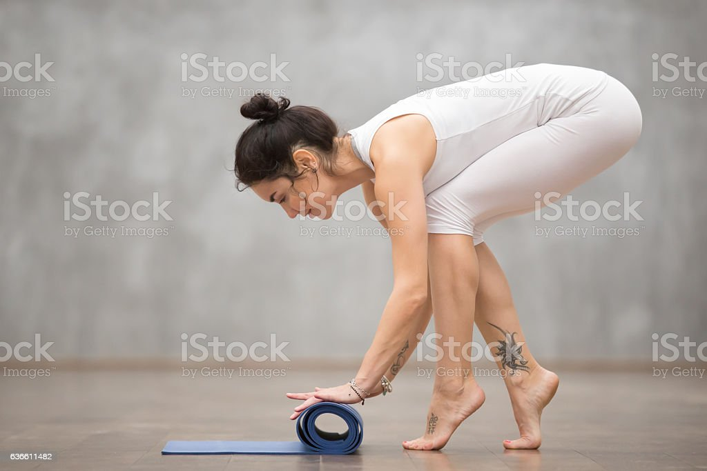Beautiful Yogi woman folding her mat stock photo