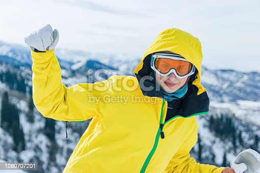 Beautiful youg woman tourist in yellow jacket, ski glasses mask and white mittens on a background of mountains looking at the camera. Winter holiday and pastime concept.