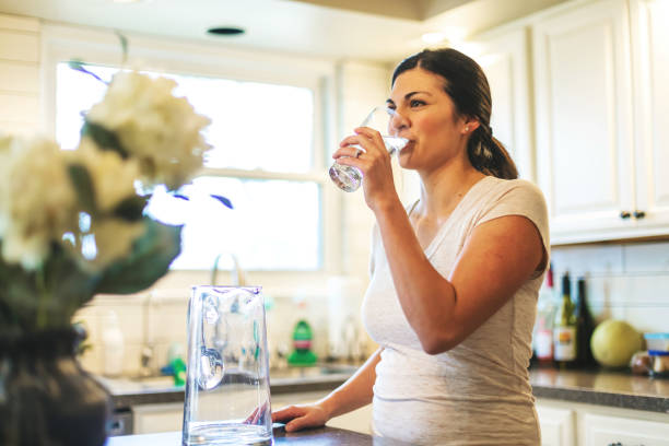 Beautiful Young Adult Millennial Female using water in residential home stock photo