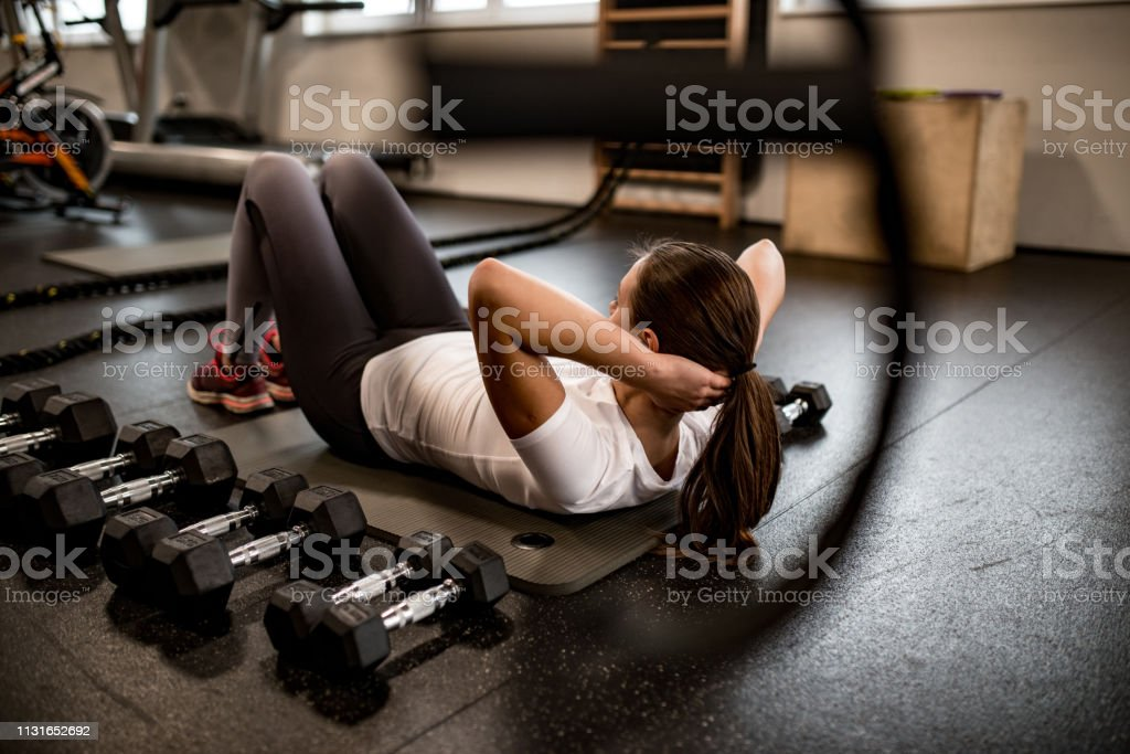 A Beautiful Young Adult Woman Doing Abdominal Floor Exercises in the...